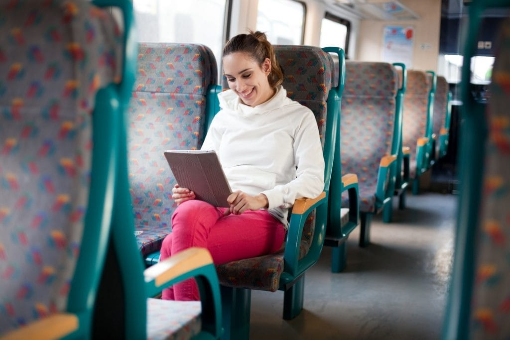 Cheerful young woman using tablet computer on the train